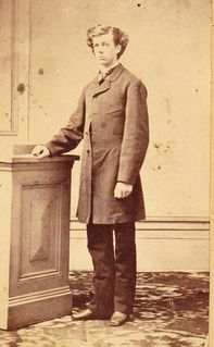 Sepia photo of Wilfrid Laurier, a student at Collège de l'Assomption. He stands to the side with his right arm on a pedestal and is looking at the camera. He wears a long jacket down to the thighs, a shirt with a white collar, a tie. black trousers and black shoes.