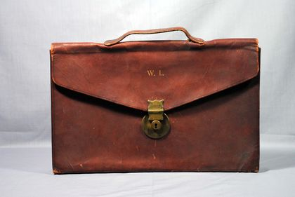 Brown leather briefcase with a rectangular flap featuring a gold metal clasp and a grip on the top. The letters W.L. (Wilfrid Laurier) are inscribed in gold at the front.