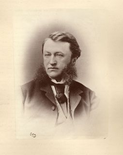 Portrait photo of Toussaint-Antoine-Rodolphe Laflamme wearing a black jacket and large tie under which may be seen a diamond motif sweater and a white shirt. He is looking to the photographer's right.