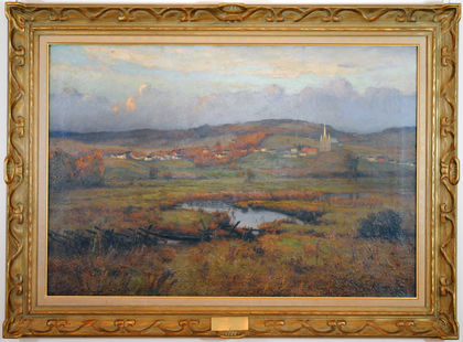 Framed painting of the church and homes of the village of Arthabaska near the top of the canvas with the sky overhead. Below the village, a field crossed by a river. The yellow, orange and green tones are indicative of the onset of fall. The gold-coloured frame features ribbon molding trim.