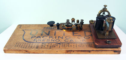 Telegraph transmitter consisting of a wooden board inscribed with United Packing Co. Fresno, Calif. and a key to tap out and receive messages in Morse Code.
