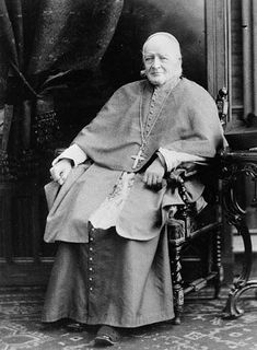 Black and white portrait of Bishop Ignace Bourget seated on a chair in a living room. He is wearing religious attire: a cassock, white skullcap and a cross around his neck.