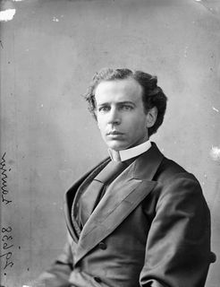 Black and white photo of Laurier seated on a chair and dressed in a suit and neck tie that seem too big for him. He is looking at and facing the photographer's right.