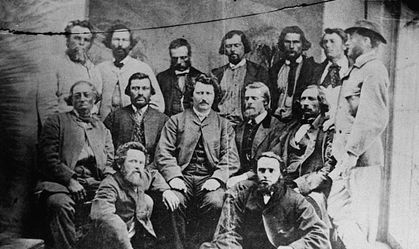 Photo of a group of Métis men from Manitoba who formed part of the Métis Nation government. Louis Riel is seated at the centre of the group, his hands on his thighs. He is wearing a suit and looking at the photographer.