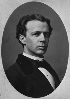 Black and white photo of Wilfrid Laurier dressed in a suit, black jacket, white shirt and black bow tie. His body and head are positioned to the side and he is looking directly at the photographer.