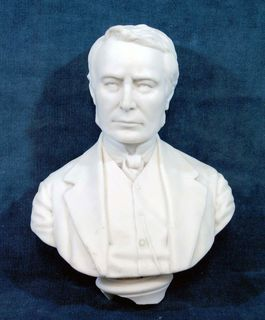 White bust of Mr. Blake's head and shoulders. He is wearing a jacket and a bow tie.