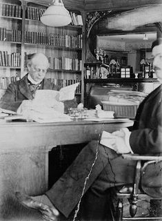 Black and white photo of Laurier seated at his desk reading a document. Behind him, a large bookcase and a mirror. Facing him, a man seated in a chair (Mr. Boudrias).