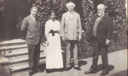 Black and white photo taken at the home (in the background) of the Honorable Sydney Fisher. From right to left: the Honorable Sydney Fisher in a black suit; W. Laurier in a grey suit, holding a cane; Mrs. Arthur Branchaud in a white dress and Mackenzie King in a grey suit.