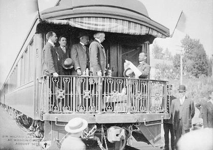 Black and white photo of Laurier and a group of men standing on the rear balcony of a railway car. Another man standing on the railway car's stairs is facing Laurier and reading a text. A crowd surrounds the car.