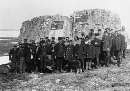 Black and white photo of Captain Joseph-Elzéar Bernier, his crew and a sheep assembled for a group photo. Behind him is a huge rock on which is installed a commemorative plaque and the Canadian flag at the time. The ocean lies behind the huge rock.