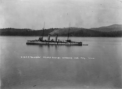 Black and white photo of a metal ship with a mast at each end and two chimneys at the centre towing a small wooden boat behind. Behind the ship is the forest forest that characterized the port of Prince Rupert in 1914.