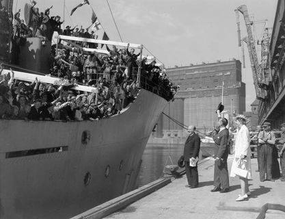 A man and a woman on a wharf greeting a large group of men and women on a metal ship.