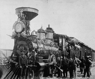 Photo of a locomotive with a funnel, decorated with garlands and Queen Victoria's coat of arms for her Jubilee. The locomotive pulls several wagons. A group of men alongside the train.