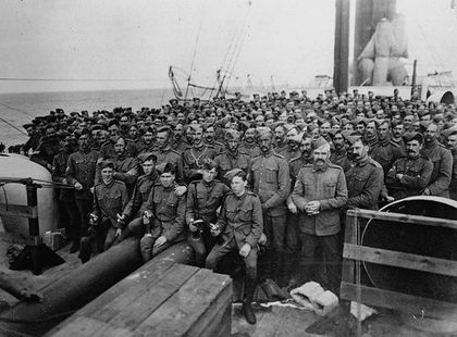 Group of soldiers on the deck of a ship looking towards the camera. They are all wearing military attire.