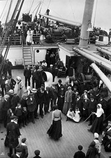 Group of men, women and children on a ship's deck. Some form a circle to watch a woman skip rope. They are passing the time during the trip to Canada.
